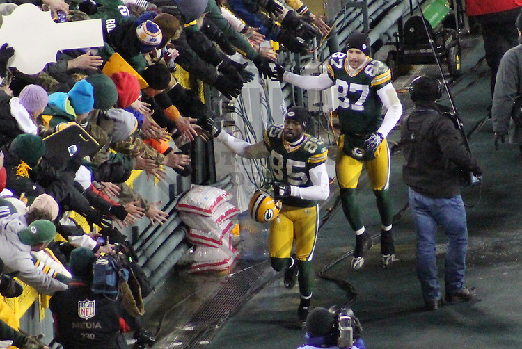 GREEN BAY - JANUARY 2011: Greg Jennings (85) and Jordy Nelson (87) of the Green Bay Packers high five fans after a game on January 2, 2011 at Lambeau Field in Green Bay, Wisconsin. (Photo by Brad Krause)