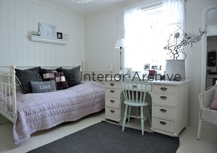 This antique style child's bedroom is furnished with an IKEA iron bed and an elegant painted desk with drawers