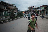 Srinagar, India-August 8, 2010: Kashmiri children and teenagers retreat after throwing rocks at Indian police and military in downtown Srinagar