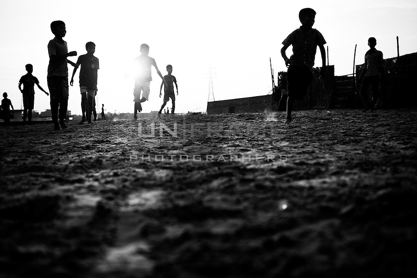 Children play football in a field near to a tannery in Hazaribagh area. Hazaribagh is one of the most polluted areas in the world.  Tanneries in the city's Hazaribagh area discharge more than 30000 square meters of liquid waste every day. The tanneries discharge the effluents into the river system causing a large area of acid sludge. Dhaka, Bangladesh.