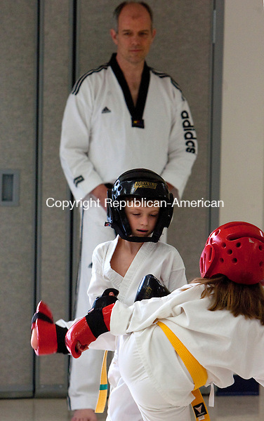 SOUTHBURY, CT 28 JUNE, 2010-062810JS01-Instructor Master William Evans, a 4th degree black belt, looks on as Ryan Paltauf, 7, of Southbury spars with Alison MacDougall, 5, of Southbury during a karate class at the Southbury Parks and Recreation building in Southbury on Monday. The mid-rank class runs on Monday's and Wednesday's year round. <br /> Jim Shannon Republican-American