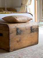 In the master bedroom an antique chest of plain pine serves as additional storage while a cushion creates a simple seat