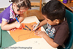Education preschool art activity 3 year olds boy and girl drawing with markers drawing on same piece of paper horizontal handedness girl using right hand boy using left hand