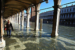 A lady walks with boots on flooded streets at St Mark's square during an acqua alta (high-water). The Acqua Alta, a convergence of high tides and a strong sirocco, reached 125 centimetres in Venice, on November 20, 2013.  <br /> <br /> &copy; Pierre Teyssot