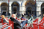 A tourist with boots takes a sun bath on flooded St Mark's square during an acqua alta (high-water). The Acqua Alta, a convergence of high tides and a strong sirocco, reached 125 centimetres in Venice, on November 20, 2013.  <br /> &copy; Pierre Teyssot