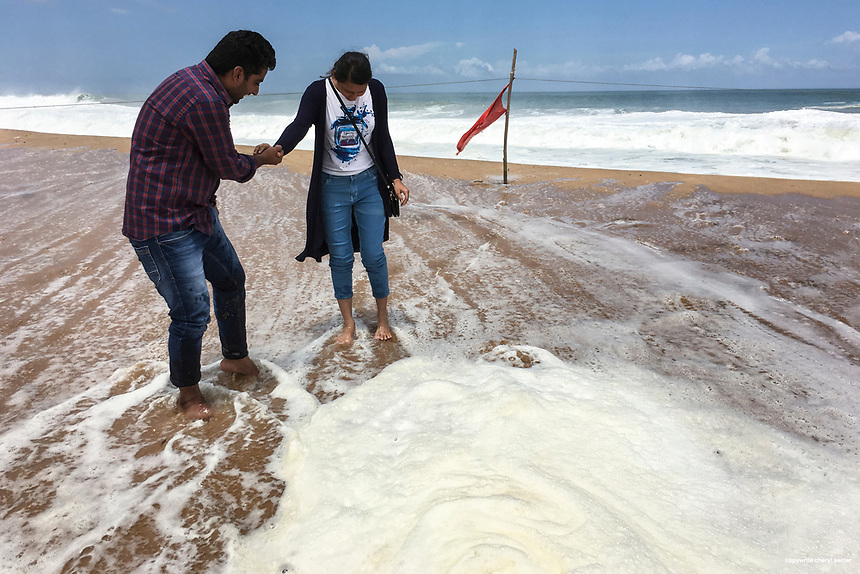 A couple visiting Poovar Golden Beach let waves from the Indian Ocean ways over their feet in Thiruvananthapuram,  Kerala, India  June 6, 2017 (Cellphone Photo by Cheryl Senter)