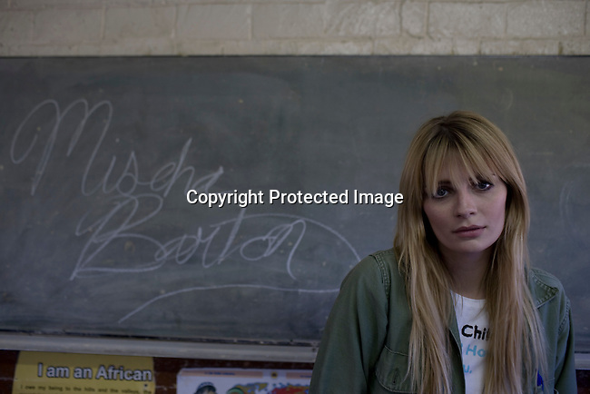 SOWETO, SOUTH AFRICA - SEPTEMBER 1: Mischa Barton, the actress and model, writes her name on a board in a classroom at Winnie Ngwevekazi Primary School on September 1, 2008 in Soweto, outside Johannesburg, South Africa. Mischa Barton spent 2 days visiting Save The Children supported projects in South Africa, meeting school children and young children. Save The Children are helping about 51,000 children made by HIV/AIDS and poverty to access food, healthcare, social security and education. (Photo by Per-Anders Pettersson/Getty Images For Save The Children).