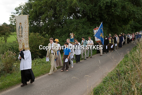 Walsingham Pilgrimage.  Roman Catholics, walk in procession from the Church of Rome, Slipper Chapel carrying a statue of Our Lady of Walsingham  into the village, of Little Walsingham where they hold mass in the grounds of the ruined Abbey and old Priory. North Norfolk, England 2006.