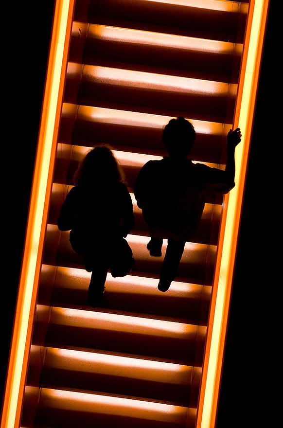 Duitsland, Essen, 12 aug 2010.Mensen lopen op trap in trappenhuis in het Ruhr Museum, museum over de industrie geschiedenis van het Ruhrgebied. Museum is gehuisvest in een oud fabrieksgebouw op voormalig terrein van kolenmijn. Er is een nieuw trappenhuis gebouwd met een rood en geel verlichte trap..Foto Michiel Wijnbergh.. Staircase in museum Ruhr Museum.