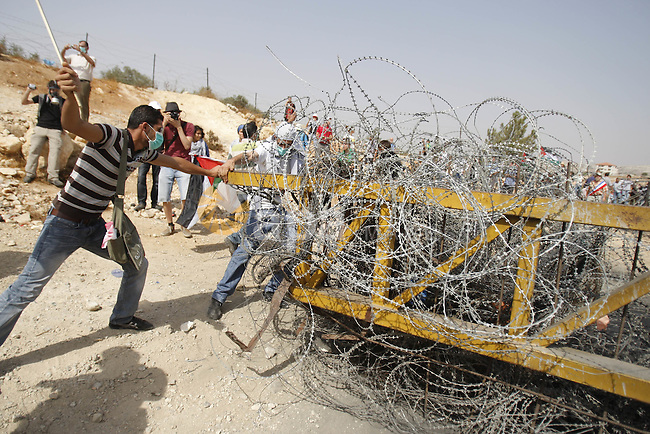 Palestinians and foreign protestors try to avoid the israeli separation barrier during a demonstration against Israel's separation barrier in the West Bank village Bilin near Ramallah on July3, 2009. Photo by Nedal Shtieh