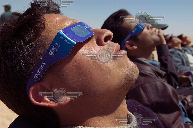 Middle class Libyan youths observe a total solar eclipse. Thousands of tourists travelled to the Sahara desert to witness the eclipse. Protective glasses were issued, which were sponsored by the British Council and the Libyana mobile telephone company.