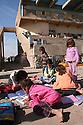Iraq 2007 .Displaced Kurdish families in the stadium of Kirkuk, children reading their school books .Irak 2007 .Familles  kurdes deplacees dans le stade de Kirkouk, enfants avec leurs livres d'ecole