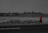 Africa, donna vestita di rosso cammina lungo una strada<br /> <br /> Afrique, femme habillée en rouge marche dans une rue Africa, woman in red walking down a street