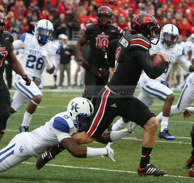 Kentucky Wildcats wide receiver Javess Blue (8) tackles UL safety Gerod Holliman during the first half of the University of Kentucky vs. University of Louisville at Papa Johns Cardinal Stadium in Louisville, Ky., on Saturday, November 29, 2014. UL won 44 - 40. Photo by Tessa Lighty | Staff