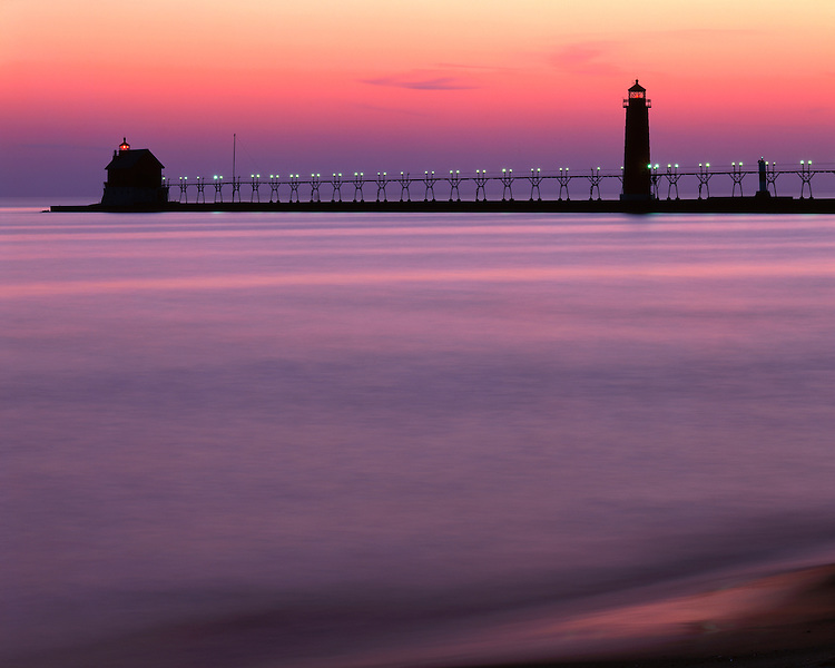 Sunset glow on Grand Haven Lighthouse on the shore of Lake Michigan; Grand Haven State Park, MI