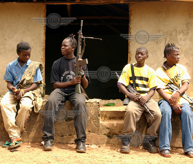 Soldiers in Charles Taylor's army sit along the road to Sierra Leone, on the same day that a ceasefire was signed..The ongoing conflict in Libera intensified in March 2003 when rebels opposed to the government of Charles Taylor gained territory across much of the country, advancing on the capital city Monrovia. In August 2003 Taylor agreed to hand over power to an interim government and went into exile in Nigeria, which led to the signing of a peace agreement. Taylor was indicted for war crimes by a UN court in Sierra Leone, accused of fuelling conflict across several West African countries.