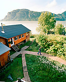 USA, Alaska, man walks on a path at a fishing lodge in Redoubt Bay, Redoubt Bay Lodge