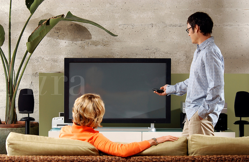 Couple checking out large screen TV and entertainment system.