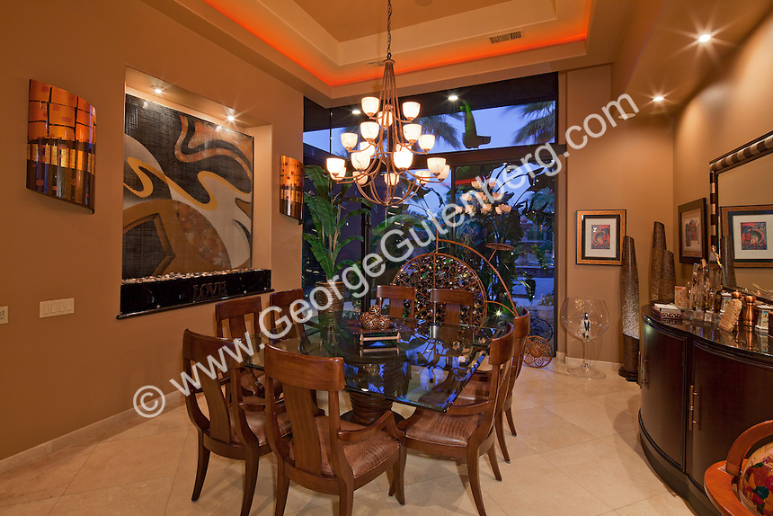 Luxurious large dining room is seen at night with lighted cove