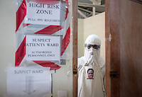 "Hygienist Morris Zolu looks out from the ""red zone"" wearing his PPE Portrait Project photo at ELWA II ETU in Monrovia, Liberia on Sunday, March 1, 2015. The ""red zone"" is where health care workers tend to Ebola patients. Occidental College professor Mary Beth Heffernan's PPE Portrait Project involves photographing health care workers and making disposable, adhesive prints of their images, which are then placed on the worker's PPE.<br /> (Photo by Marc Campos, Occidental College Photographer) Mary Beth Heffernan, professor of art and art history at Occidental College, works in Monrovia the capital of Liberia, Africa in 2015. Professor Heffernan was there to work on her PPE (personal protective equipment) Portrait Project, which helps health care workers and patients fighting the Ebola virus disease in West Africa.<br />