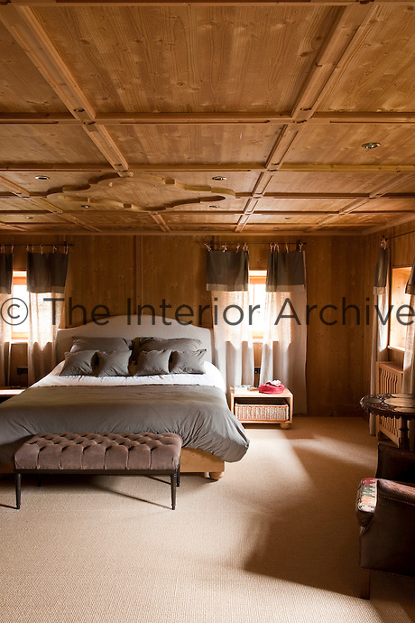 The master bedroom features a contemporary coffered ceiling and is furnished in muted shades