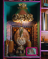 A niche in the bookcase houses an exotic lamp and a collection of objects including a photograph of Zandra Rhodes