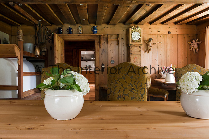 Freshly cut Hydrangea in white pots decorates the simple wooden table in the traditional 'stube'