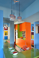This open plan kitchen has a 1950s air about it, with its multi-coloured, lacquered kitchen cabinets and work surfaces