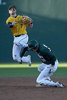 Justin Antoncic (18) of the Michigan State Spartans is out as shortstop Nick Shumski (7) of the Merrimack Warriors turns a double play in a game on Saturday, February 22, 2020, at Fluor Field at the West End in Greenville, South Carolina. Merrimack won, 7-5. (Tom Priddy/Four Seam Images)