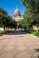 Capitol of Texas Great Walk 2 - The Texas Capitol in downtown Austin through the trees from the South view with this wonderful  blue sky and pattern limestone walkway which is called the Great Walk . The Capitol of Texas is located in downtown at Congress ave facing toward south congress from this view. The Capitol building is an impresses building with it large dome done in the Renaissance Revival architecture with the red granite from Granite Mountain and the rest of the capital in Oak Hill Limestone.