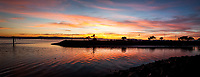 A two-image panoramic view of sunset glowing orange and gold and reflecting in the waters of the San Leandro Marina channel into San Francisco Bay.