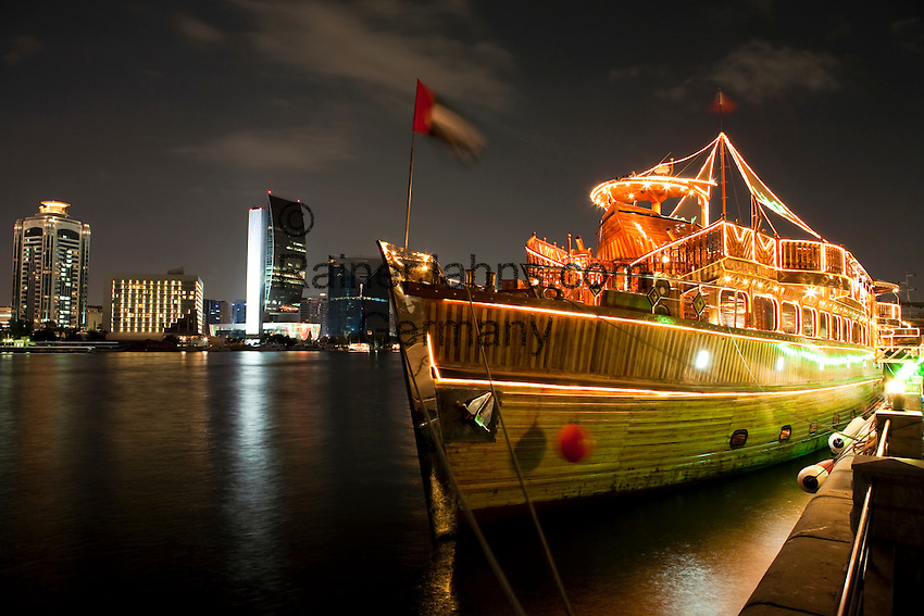United Arab Emirates, Dubai: View over the Dubai Creek with the National Bank of Dubai building, dinner cruise dhow lit up at night