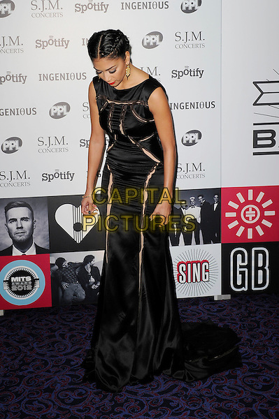 Nicole Scherzinger.Attending the Music Industry Trusts Award, Grosvenor House, London, England..5th November 2012.MITS full length black sleeveless dress slash slashed cut out away braid plait   looking down.CAP/MAR.© Martin Harris/Capital Pictures.