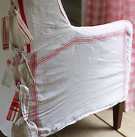 A loose cover fashioned out of recycled red and white tea towels on an old armchair