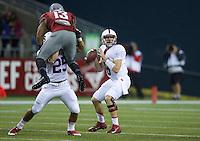 SEATTLE, WA - September 28, 2013: Stanford quarterback Kevin Hogan dropbs back to pass as tam mate running back Tyler Gaffney Stanford blocks Washington State linebacker Darryl Monroe during play at CenturyLink Field. Stanford won 55-17