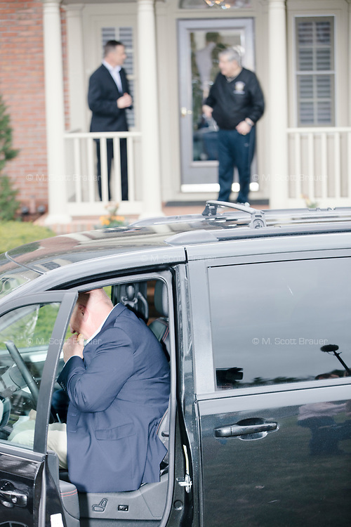 A security guard eats a cookie while exiting the vehicle after Democratic presidential candidate and South Bend mayor Pete Buttigieg arrived to speak at a house party with the Bedford Democrats in Bedford, New Hampshire, on Sat., Apr. 20, 2019. The candidate stood on a chair throughout his speech.