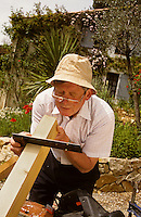 Home handyman checking the square of a piece of timber outside in his garden..