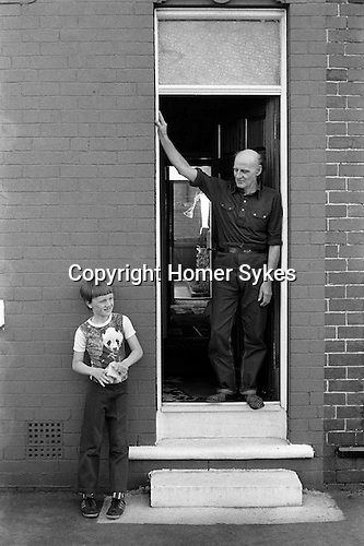 Retired miner Charlie Hayward. He spent 49 years at South Kirkby colliery and son at front door looking straight through to the back garden. South Kirkby Colliery, Yorkshire England. Coal Miners story 1979.<br />