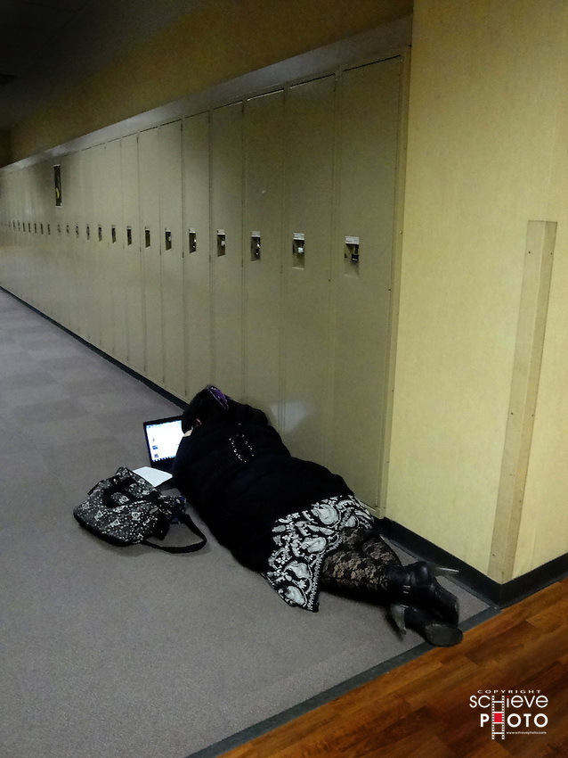 A college student studies on a lap top laying in the school hallway.
