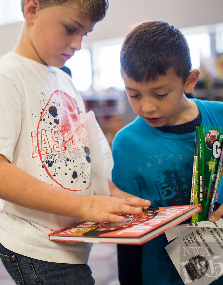 NWA Democrat-Gazette/CHARLIE KAIJO Pearson Wright, 8 and Chris Lopez, 8 look at books on Monday, October 23, 2017 at the Scholastic Book Fair at the Osage Creek Elementary and Creekside Middle School library in Bentonville. The fair continues until Friday, and proceeds go to benefit the schools' library. The library is also collecting donations to buy books for the Benton County Sunshine School's library.