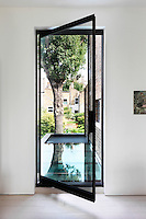 A full height glazed pivot door and glass balustrade makes a visual connection to the glass roof of an extension and opens up views to the garden from the lounge.