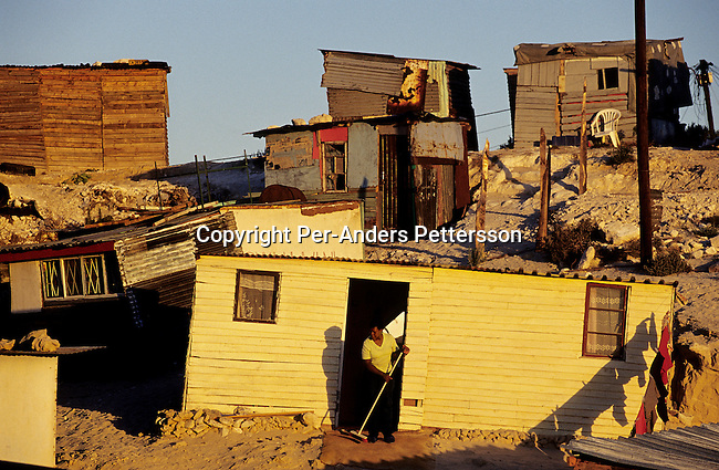 An unidentified woman sweeps outside her shack, as the sun sets on October 16, 2003 in Site B section of Khayelitsha, the biggest township outside Cape Town, South Africa. It's estimated that over one million people live here, most of them under appalling conditions in shacks with no running water or electricity. The township was founded in 1984. Most of the people don't find work and the lucky few are paid low wages used mostly as maids and day laborers. (Photo by: Per-Anders Pettersson)....