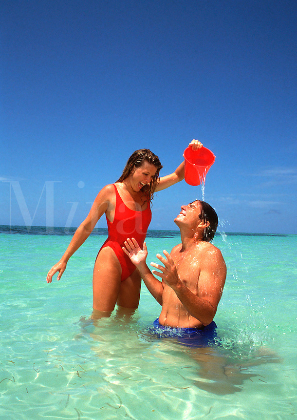 Woman pouring water on man's head at beach
