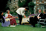 Glyndebourne Festival Opera  al fresco picnic gardens garden during interval East Sussex UK 1980s. Man in white jacket is serving the opera goers.