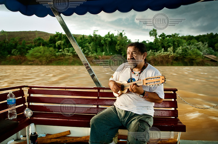 The Peruvian musician Maurizio Vicenza plays a ukelele will travelling on a riverboat on the Parana River.