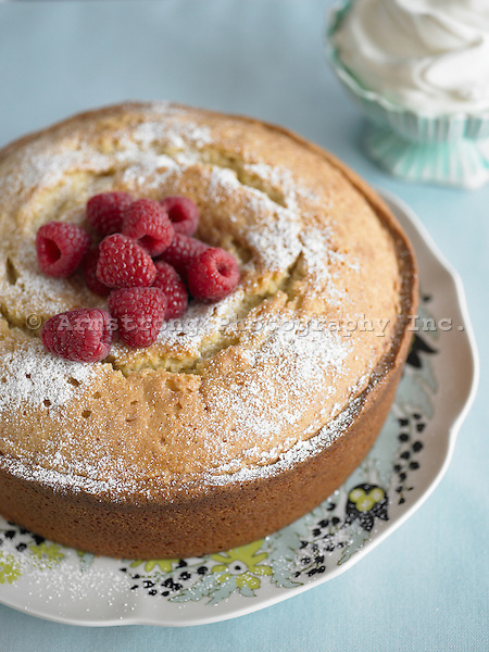 Pound cake cooked in a round bundt pan, topped with powdered sugar and fresh raspberries
