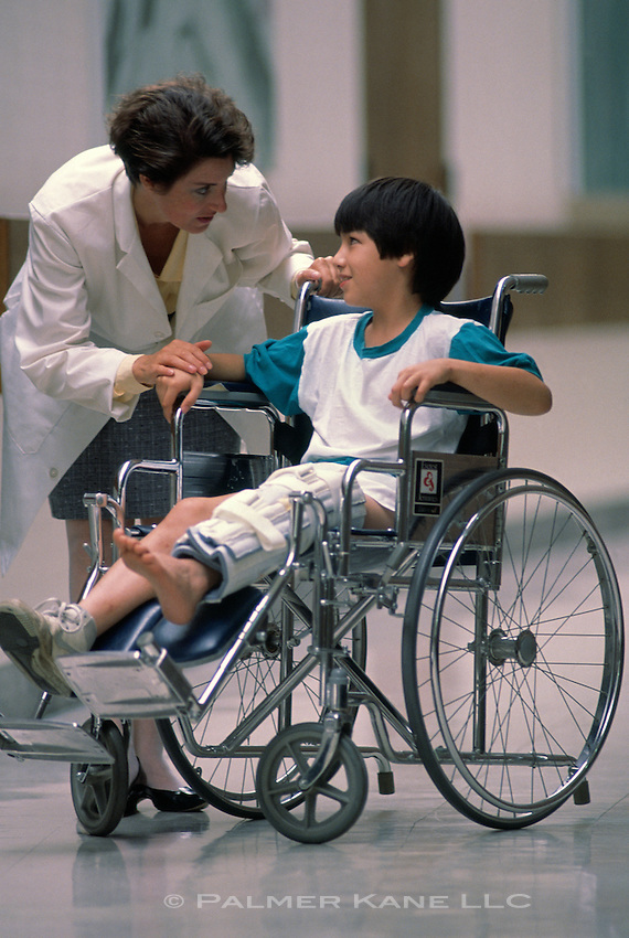 Female doctor talking to boy with leg injury in wheelchair