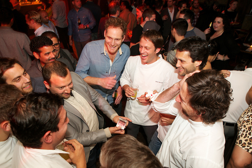 New York, NY - October 27, 2014: 'Foodie Magician' Josh Beckerman (Center-left) performs card tricks for chefs and guests at an afterparty for the International Chefs Congress, hosted by StarChefs at Gallows Green in Chelsea.<br /> <br /> CREDIT: Clay Williams for StarChefs.<br /> <br /> &copy; Clay Williams / claywilliamsphoto.com