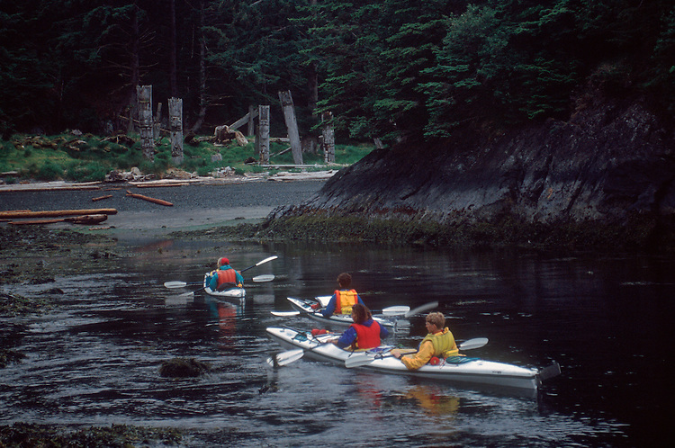 Sea Kayakers, Queen Charlotte Islands, Haida Gwaii, Haida totem poles, at the Haida village site of Skang wai, red cod village, Ninstints, British Columbia, Canada, .
