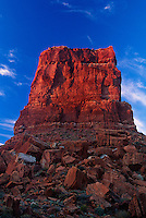 792800001 angled sunrise light illuminates a sandstone monolith under a lightly clouded sky in valley of the gods utah